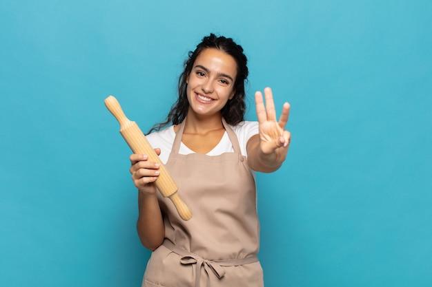 Jeune femme souriante de caucase et à la sympathique, montrant le numéro trois ou troisième avec la main en avant, compte à rebours