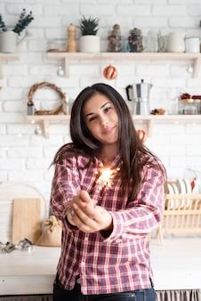 Jeune femme souriante avec un cierge magique célébrant noël dans la cuisine