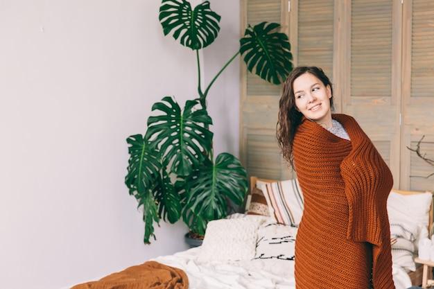 Jeune femme souriante en couverture brune restant dans la chambre. jeune fille tenant une couverture