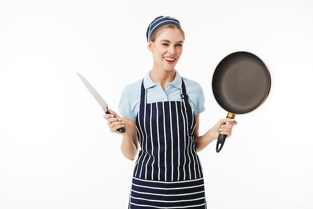 Jeune femme souriante cuisinier en tablier rayé et bonnet clignotant joyeusement pendant