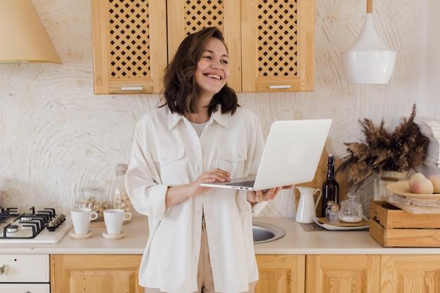Une jeune femme souriante dans une cuisine profitant d'une conversation vidéo faisant connaissance sur un site web une femme passe du temps sur un réseau social