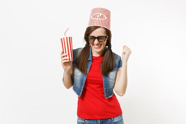 Jeune femme souriante dans des lunettes 3d avec seau pour pop-corn sur la tête en regardant un film tenant une tasse en plastique de soda ou de cola faisant le signe du gagnant disant oui isolé sur fond blanc. les émotions au cinéma.