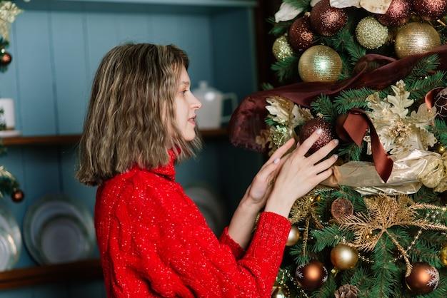 Jeune femme souriante dans un pull, vacances d'hiver à l'intérieur de la maison décorée avec arbre de noël.