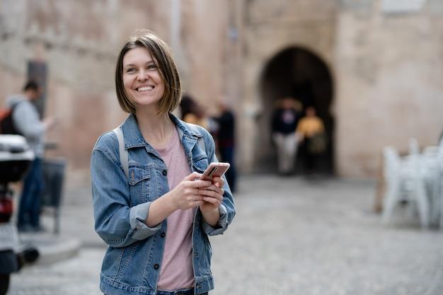 Jeune femme souriante dans la rue, tenant un téléphone. fille touristique consultant son smartphone dans la rue à la recherche d'endroits intéressants.