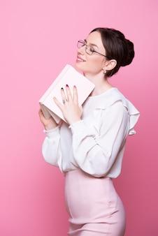 Jeune femme souriante dans des verres avec un cahier dans ses mains lève les yeux rêveusement.