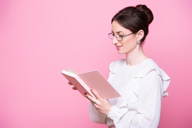 Une jeune femme souriante dans des verres avec un cahier dans ses mains lit des notes.