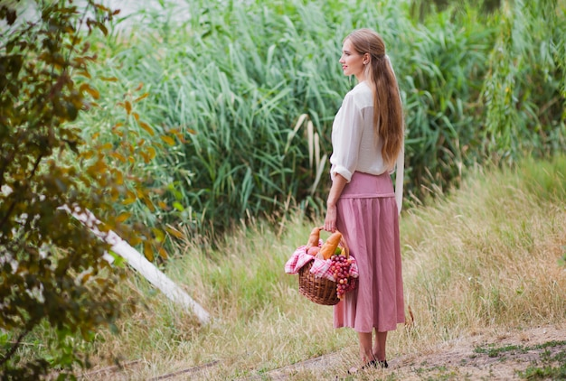 Jeune femme souriante dans des vêtements de style rétro vintage est titulaire d'un panier de pique-nique dans sa main