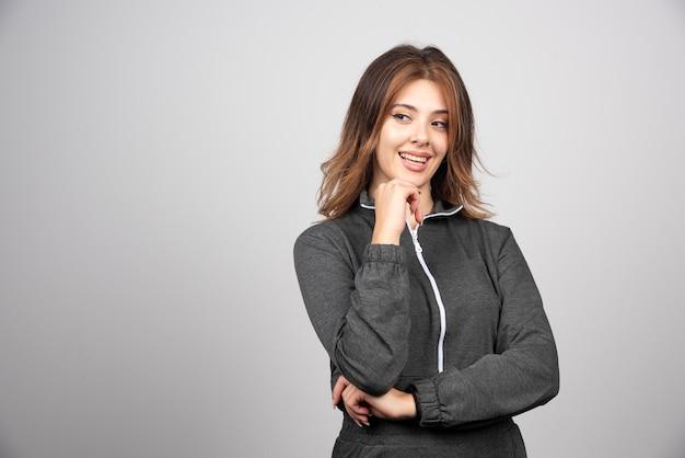 Jeune femme souriante debout et posant.