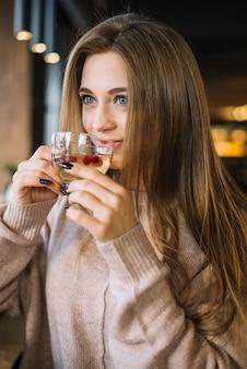 Jeune femme souriante élégante, buvant à la tasse de café