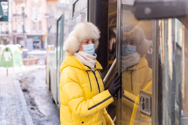 Jeune femme souriante entre dans le bus un jour d'hiver