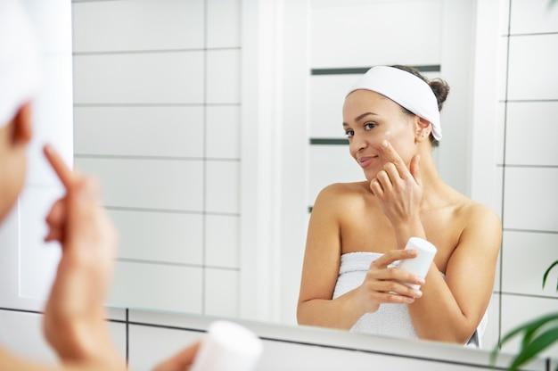 Une jeune femme souriante enveloppée dans des serviettes tenant une crème hydratante et l'appliquant sur son visage dans la salle de bain.