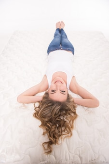 Jeune femme souriante est allongée sur le matelas de qualité.