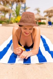 Une jeune femme souriante est allongée sur une serviette rayée sur le sable de la plage et applique de la crème solaire sur sa main.