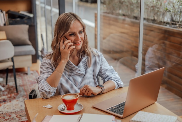 Une jeune femme souriante est assise dans un café et parle au téléphone.