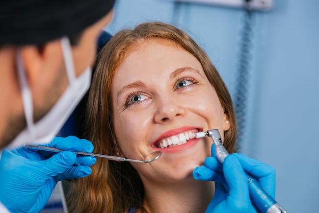 Une jeune femme souriante est assise dans une chaise de dentistes pendant que le médecin examine ses dents