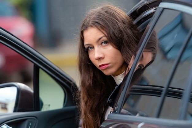 Jeune femme souriante est assise dans une voiture avec une porte ouverte et regarde en arrière