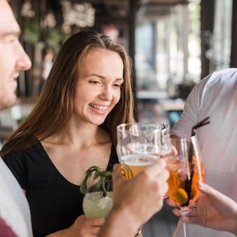 Jeune femme souriante, faire griller des boissons avec ses amis