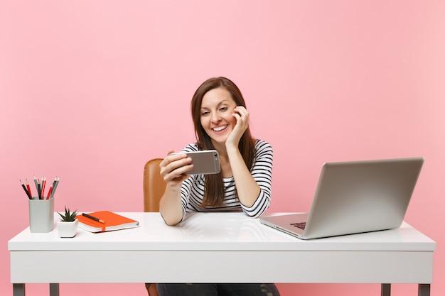 Jeune femme souriante faisant un appel vidéo en prenant une photo de selfie sur un téléphone portable tout en travaillant assis au bureau blanc avec un ordinateur portable isolé sur fond rose pastel. carrière commerciale de réussite. espace de copie.