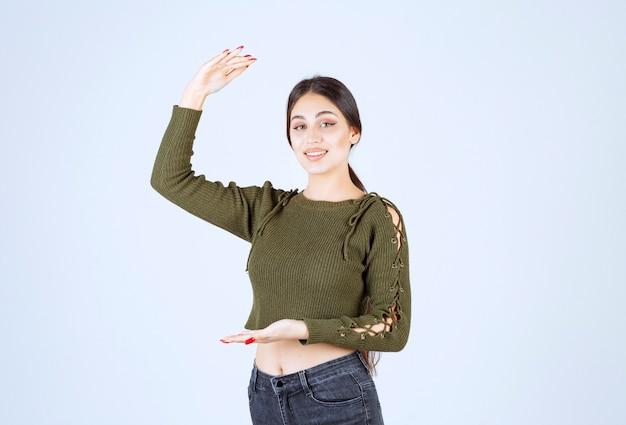 Une jeune femme souriante faisant des gestes avec les mains montrant un signe de grande et grande taille.