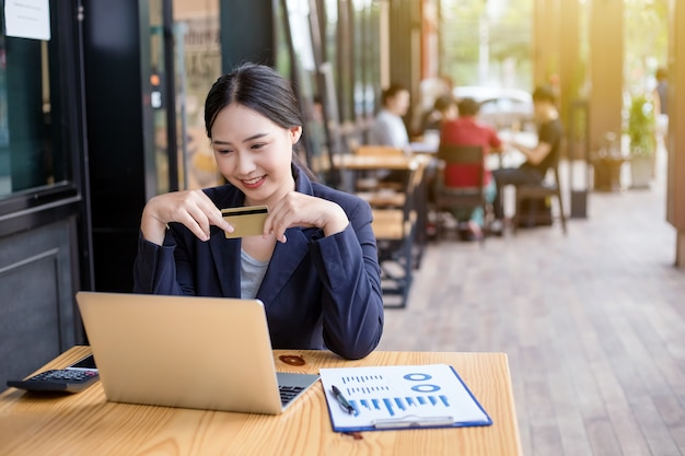 Jeune femme souriante. femme d'affaires détient une carte de crédit et d'utiliser un ordinateur portable.