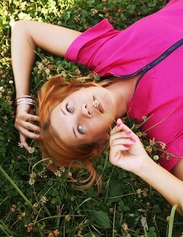 Jeune femme souriante sur l'herbe