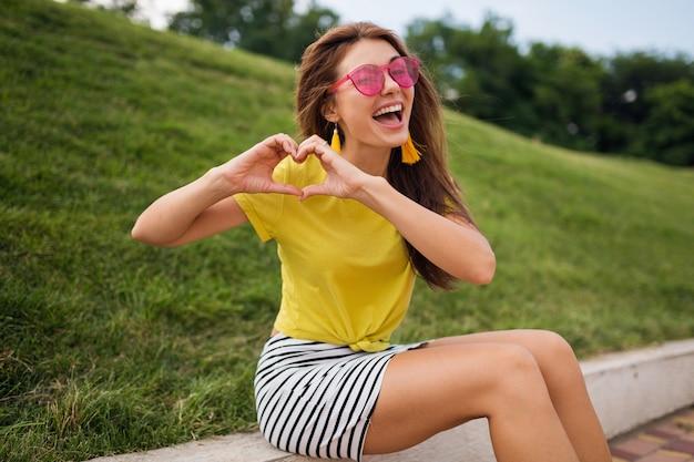 Jeune femme souriante heureuse assez élégante s'amusant dans le parc de la ville, positive, émotionnelle, portant haut jaune, mini jupe rayée, lunettes de soleil roses, tendance de la mode de style d'été, montrant le signe du coeur