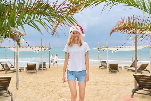 Jeune femme souriante heureuse marchant le long de la plage en bonnet de noel. vacances de noël et du nouvel an sur la côte tropicale, fond de sable de palmiers de mer océan, concept de tourisme de voyage de vacances