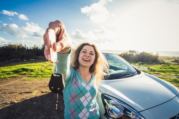 Jeune femme souriante heureuse montrant la clé de la nouvelle voiture.