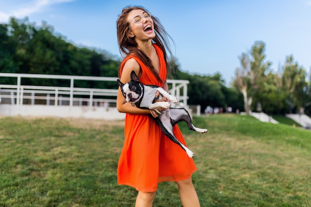 Jeune femme souriante heureuse en robe orange s'amusant à jouer avec un chien dans le parc, style d'été, bonne humeur