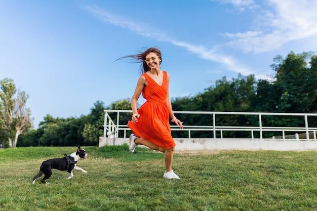 Jeune femme souriante heureuse en robe orange s'amusant à jouer à courir avec un chien dans le parc, style estival, humeur joyeuse