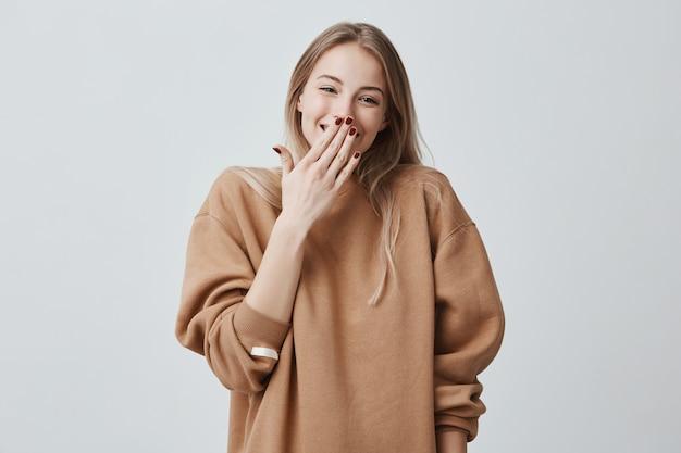 Jeune femme souriante joyeuse couvrant son visage avec la main. femme positive insouciante portant ses cheveux blonds lâches a vu une surprise préparée par son mari, debout et souriant, heureux