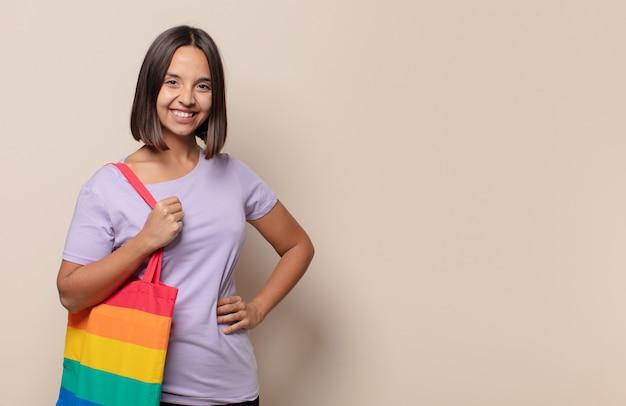 Jeune femme souriante joyeusement avec une main sur la hanche et une attitude confiante, positive, fière et amicale