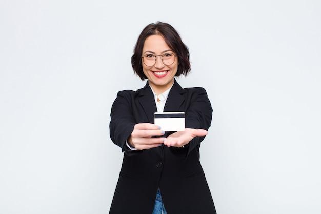 Jeune femme souriante joyeusement avec un regard amical, confiant et positif, offrant et montrant un objet ou un concept avec une carte de crédit