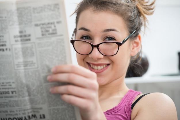 Jeune femme souriante avec des lunettes, lisant le journal