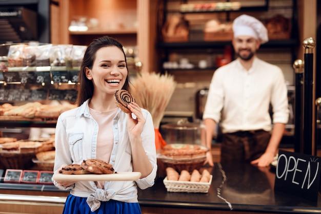 Jeune femme souriante mangeant des rouleaux dans une boulangerie moderne