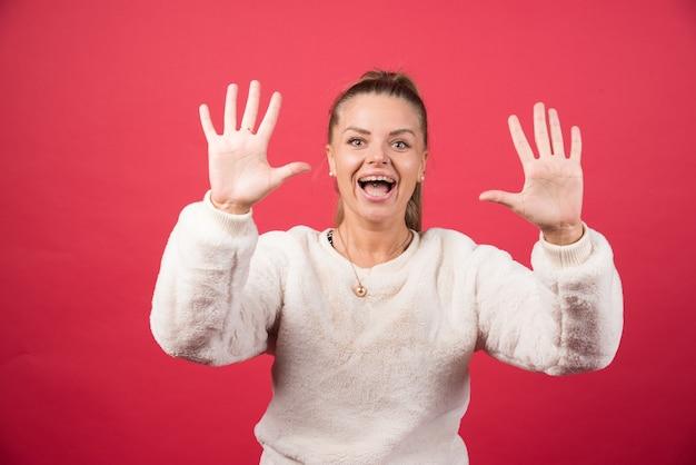 Jeune femme souriante et montrant le numéro cinq avec les doigts
