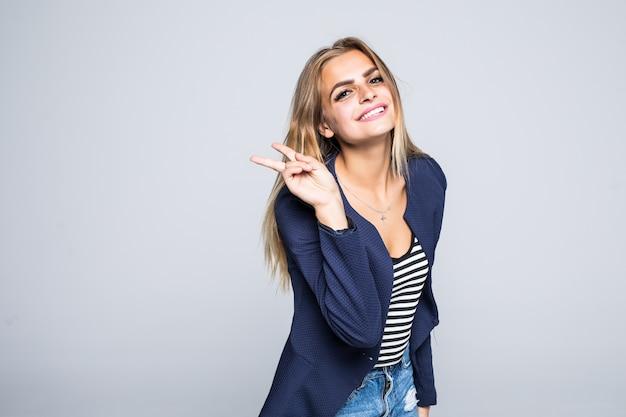 Jeune femme souriante montrant la victoire ou le signe de la paix isolé