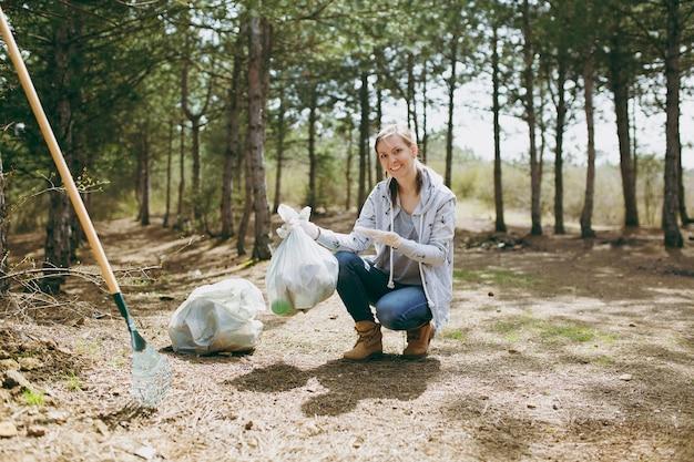 Jeune femme souriante nettoyant les ordures et pointant la main sur des sacs poubelles dans un parc ou une forêt