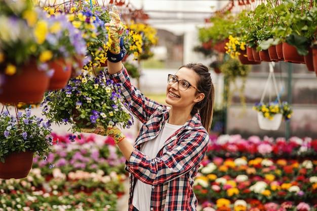 Jeune femme souriante ouvrière de jardin de pépinière debout et pot suspendu avec des fleurs.
