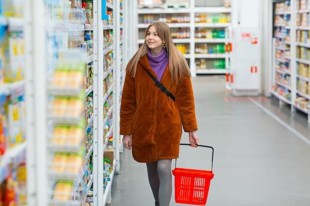 Jeune femme souriante avec un panier d'épicerie et des étagères avec des provisions dans un magasin