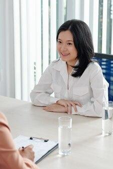 Jeune femme souriante parlant au responsable des ressources humaines, parlant de son expérience de travail et de ses compétences