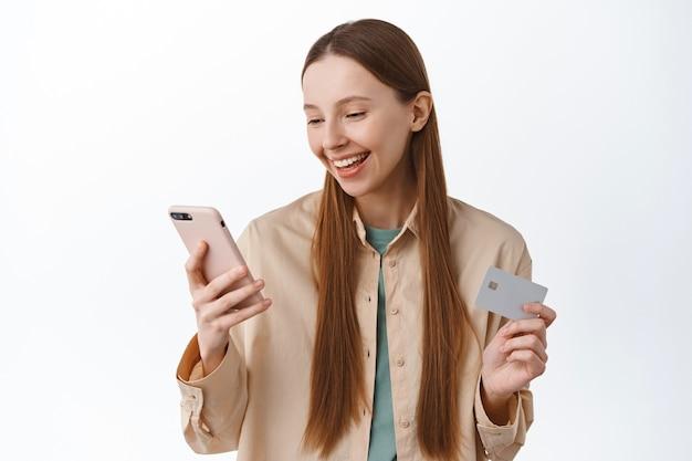 Une jeune femme souriante passe commande, paie avec un téléphone portable et une carte de crédit, regarde l'écran avec plaisir, paie, se tient sur un mur blanc.