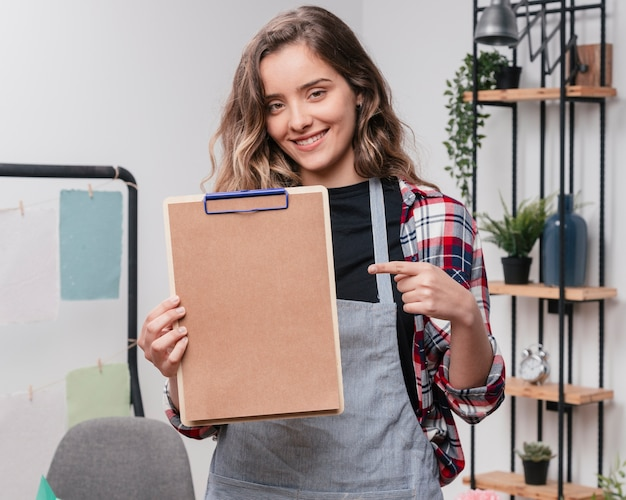 Jeune, femme souriante, pointage, index, presse-papiers