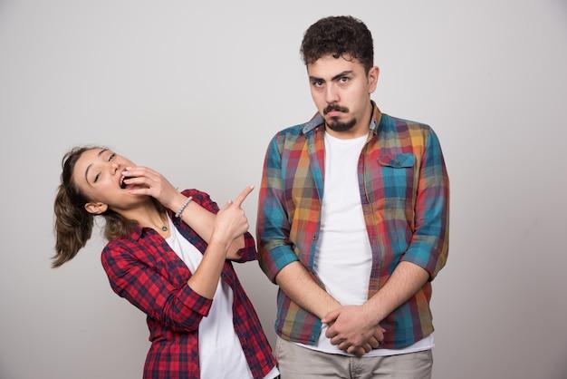 Jeune femme souriante et pointant du doigt l'homme offensé.