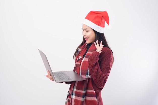 Une jeune femme souriante portant un chapeau de père noël rouge faisant un appel vidéo sur le réseau social avec la famille et les amis sur fond blanc studio.
