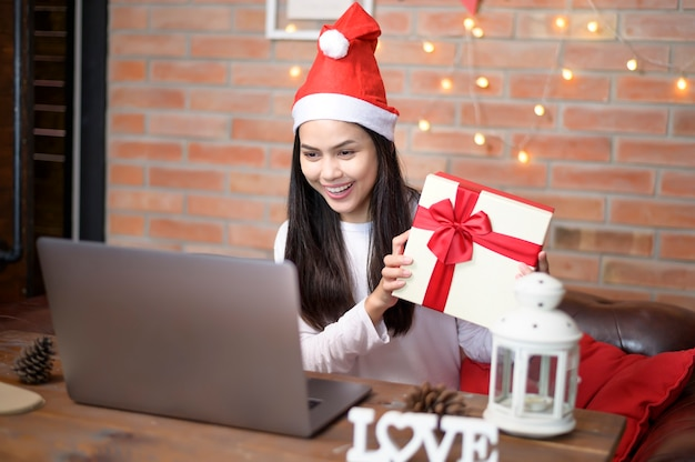 Une jeune femme souriante portant un chapeau de père noël rouge faisant un appel vidéo sur le réseau social avec la famille et les amis le jour de noël.