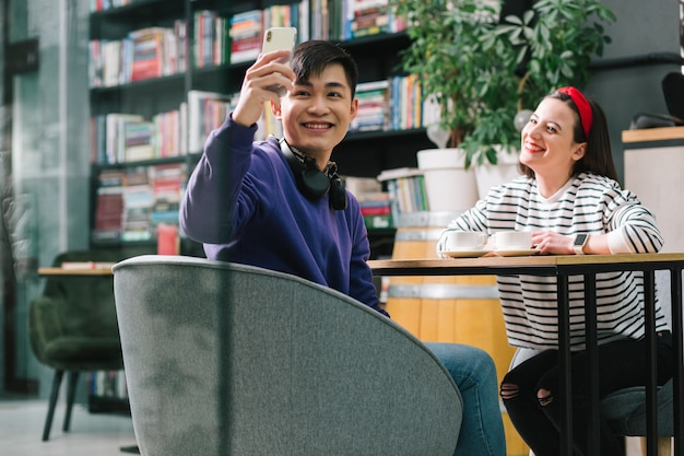 Jeune femme souriante et posant à la table avec des tasses de café pendant qu'un petit ami heureux prend des photos avec elle