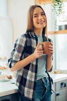 Jeune femme souriante positive avec une tasse à la maison heureuse