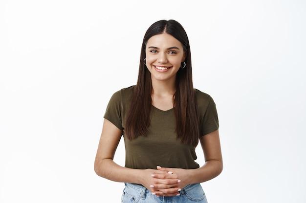 Jeune femme souriante prête à offrir son service, comment puis-je vous aider, les mains serrées et l'air amical à l'avant, mur blanc