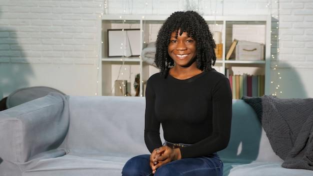Jeune femme souriante en pull noir assis sur le canapé